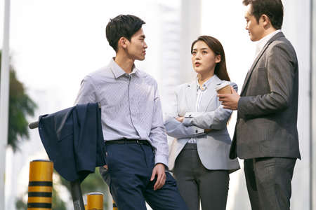 three asian business people chatting on street in downtown of modern city
