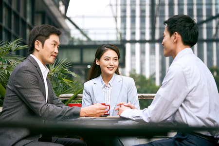 three asian corporate businesspeople discussing business outdoors in coffee shot 免版税图像