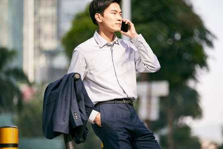 young asian businessman standing next to his electric scooter on street making a call using cellphone in downtow of modern city 免版税图像