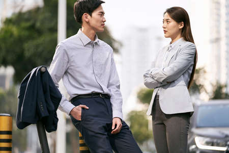 two asian business people chatting on street in downtown of modern city