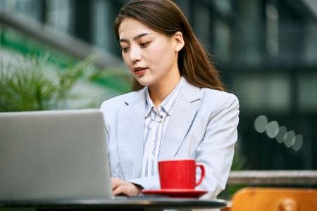 young asian businesswoman working outdoors in coffee shop using laptop computer