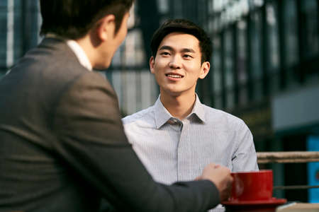 two asian corporate businesspeople discussing business at a outdoor coffee shop 免版税图像