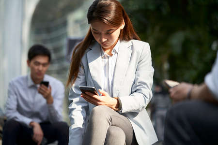 asian business woman looking at mobile phone outdoors