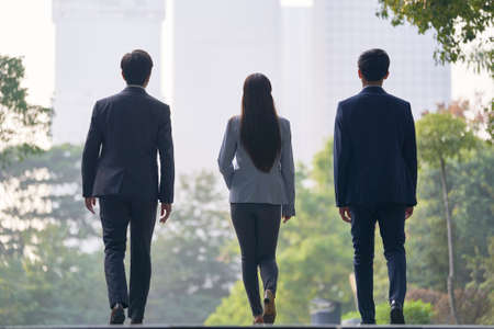 rear view of three young successful asian business people walking on street 免版税图像