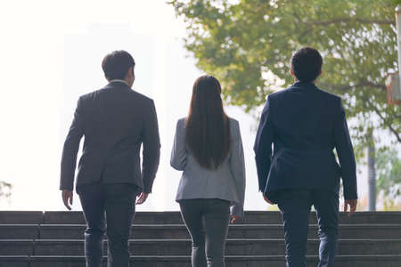 rear view of three young successful asian business people ascending steps 免版税图像