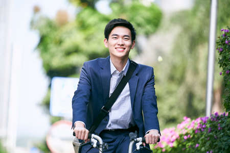 young asian business executive commuting by bike happy and smiling