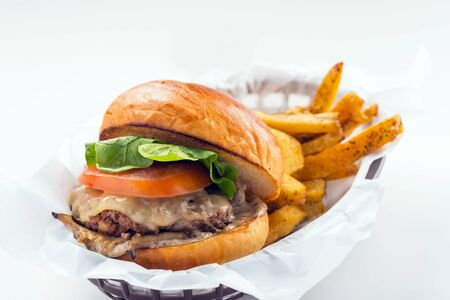 Hamburger consists of tomato and lettuce with french fries meal served on black plastic bowl