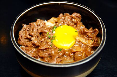 Japanese food beef gyudon with raw egg yolk and rice in black bowl