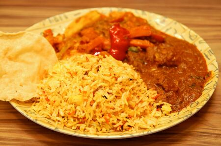 Hot curry with pita bread and biryani rice meal in a plate 版權商用圖片