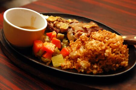 Brown rice with beef and mixed vegetables in sizzling plate