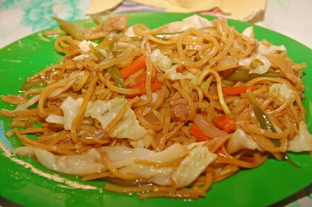 Pancit noodles with mixed vegetables on plate serve in the eatery in Philippines