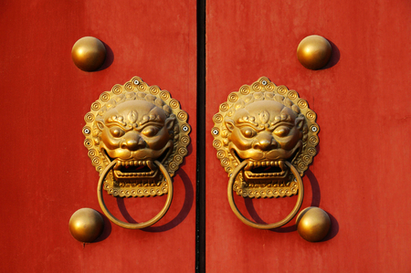 holder for door knocker and copper nails on a red door photo