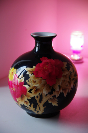 Black porcelain vase with red flower photo