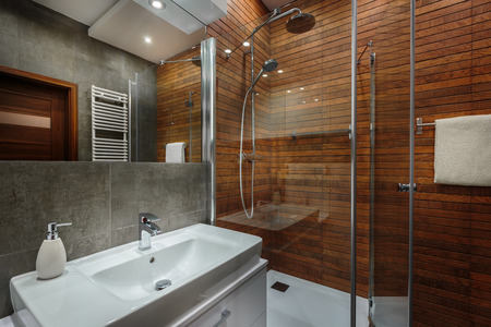Wooden wall in shower and grey tiles in new bathroom