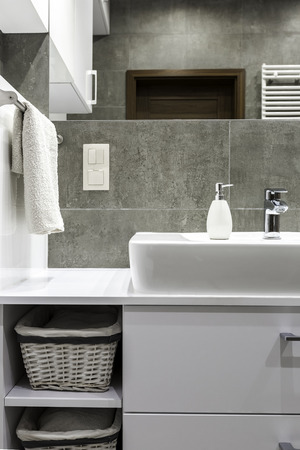 bathroom tiles: White furniture and grey tiles in modern bathroom