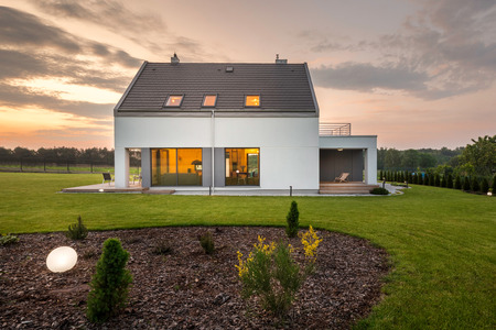 Photo of elegant white villa with backyard