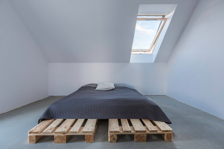 attic window: Big bed in eco style standing in light attic with window