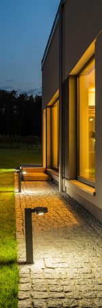 outdoor lighting: Vertical panorama of new villa with backyard and outdoor lighting, night external view