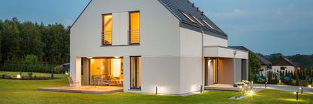 Grande casa luce nel nuovo design con ampio prato e l'illuminazione esterna, vista panoramica notturna Archivio Fotografico