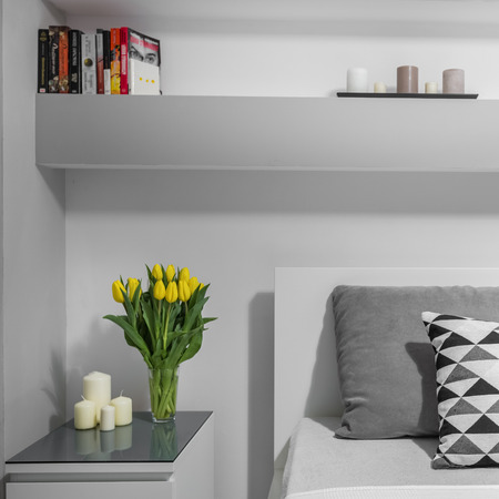 nightstand: Yellow tulips on nightstand in modern grey bedroom