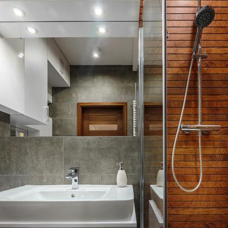 Ducha con la pared de madera como un diseño moderno en el baño Foto de archivo