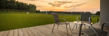 Panoramic view of new villa patio with simple furniture set, sunset view