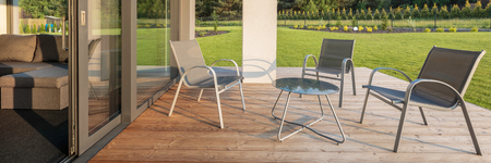 patio furniture: Panoramic view on stylish patio with wood flooring, garden view and simple patio furniture set