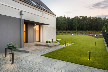 New villa with garden and decorative outdoor lighting, external view Фото со стока