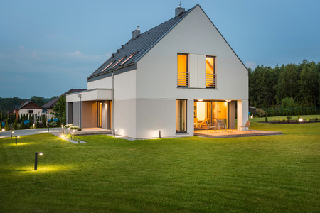 Big light house in new design with wide lawn and outdoor lighting, night view Standard-Bild