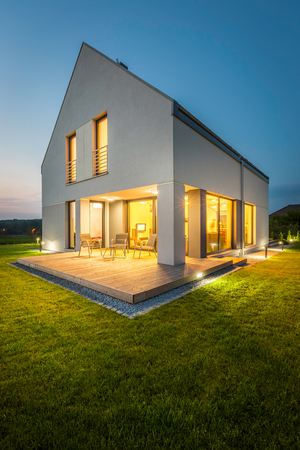 New stylish home with wide lawn and decorative outdoor lighting, external view