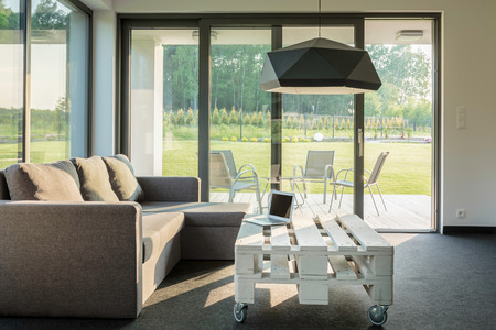 small table: Modern interior with sofa, small table and glass wall system, room with garden view, laptop lying on a small table