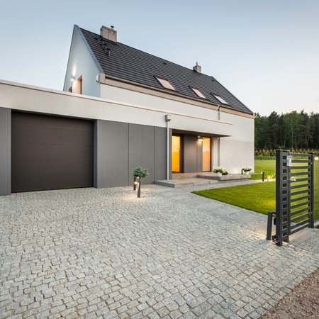 Stone driveway, garage and big garden at design house, external view
