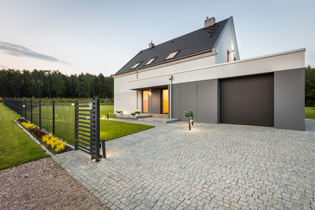 Stylish villa with fence, garage and stone driveway, external view