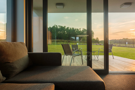 Close Up Of A Sofa, In The Background Glass Wall And Patio With Outdoor  Furniture