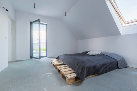 balcony window: Spacious and light empty attic bedroom with DIY bed, window and open balcony doors Stock Photo