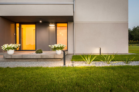 Contemporary house with garden and outdoor decorative lighting, external view