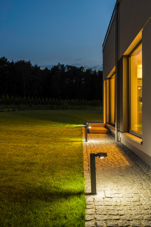 New villa with backyard and outdoor lighting, night external view Banco de Imagens