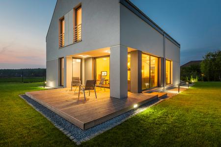 Veduta esterna di una nuova casa di notte con patio e illuminazione esterna