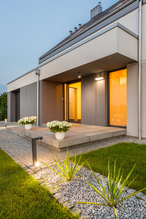 Beautiful modern villa with backyard and decorative outdoor lighting, external view Banco de Imagens