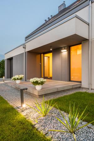 Preciosa casa con patio trasero y la iluminación exterior decorativa, vista externa