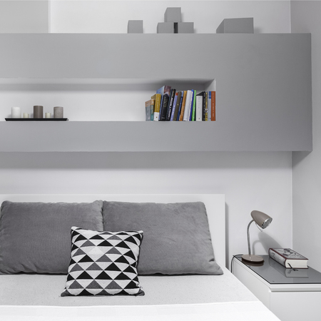 nightstand: Book on nightstand in modern, grey bedroom
