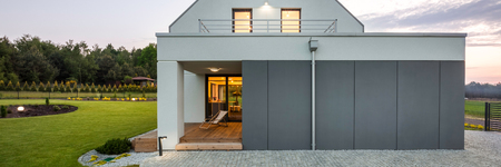garage on house: Modern house with garage, stone driveway, stylish garden and decorative outdoor light, panorama