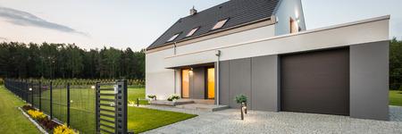 Vista exterior de la casa unifamiliar elegante con la cerca, garaje, calzada de piedra y el jardín, panorama Foto de archivo