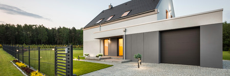 External view of stylish family house with fence, garage, stone driveway and garden, panorama