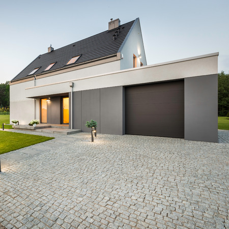 garage on house: External view of stylish house with big garage and stone driveway