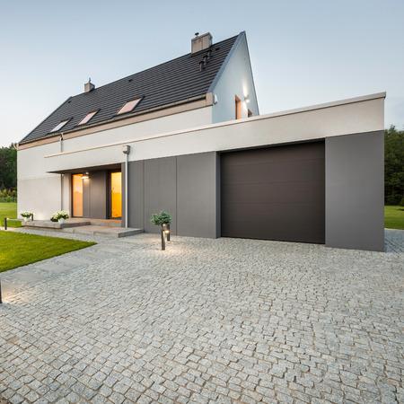 Vue extérieure de la maison élégante avec grand garage et de pierre allée Banque d'images - 59566460