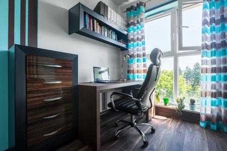 functional: Functional home office with dark wooden furniture, comfortable chair and decorative window curtains Stock Photo
