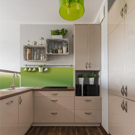 Eleganti mobili beige in cucina con elementi verdi