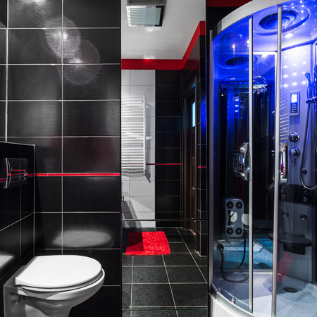 hydromassage: Stylish dark bathroom with simple white toilet and fancy shower with hydromassage Stock Photo