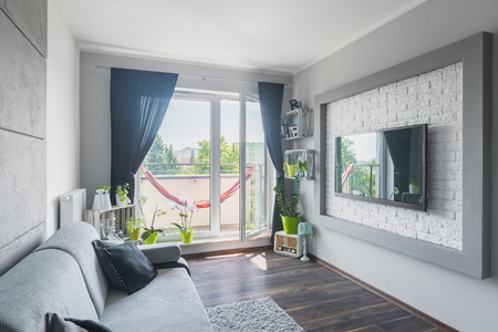 decorative balcony: New home interior with sofa, big tv, decorative wall effect and balcony Stock Photo